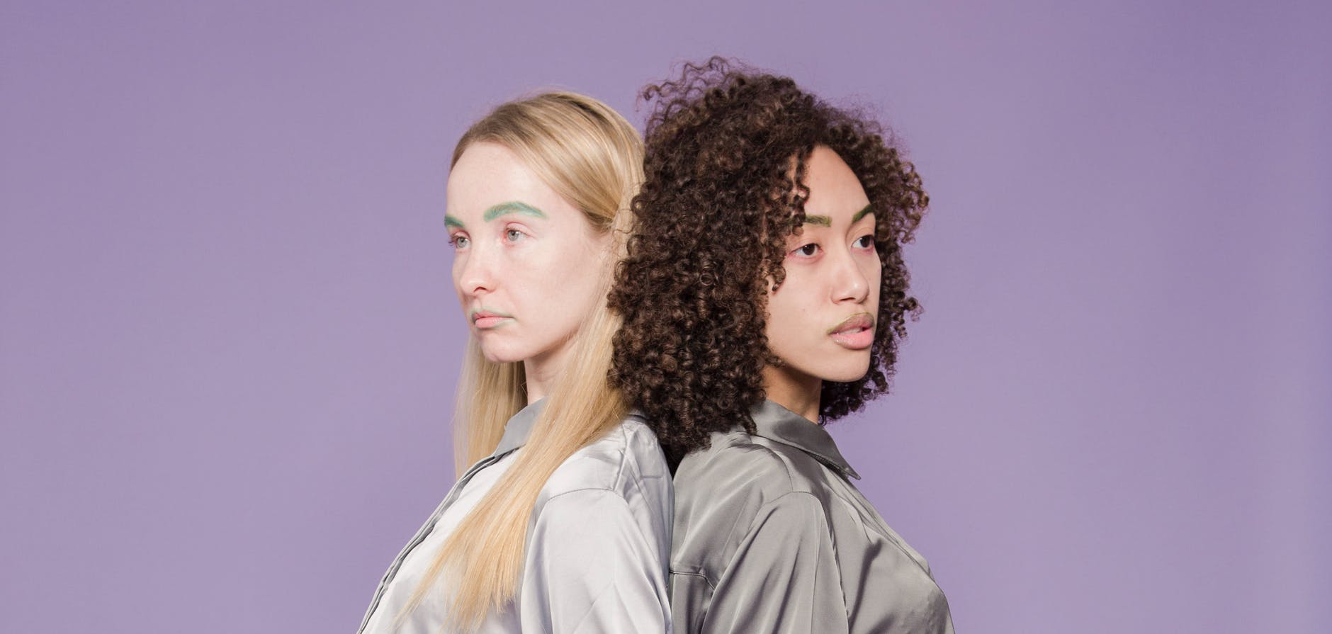 unhappy multiethnic women standing back to back in studio